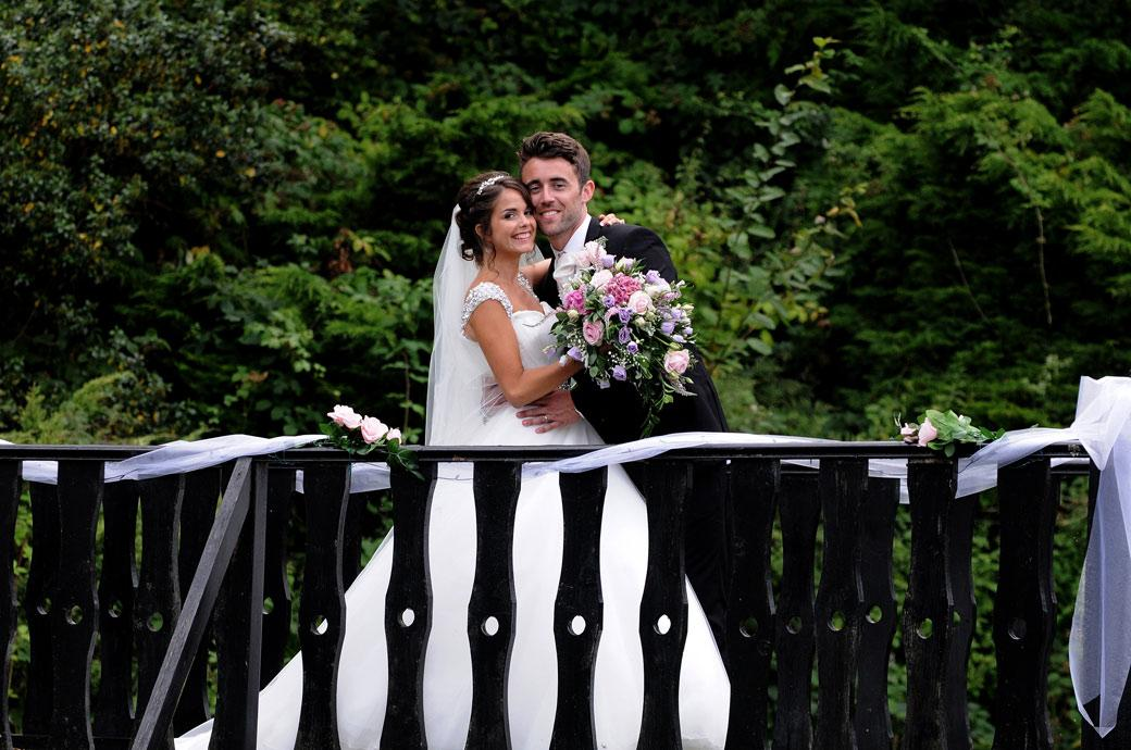 Head to head and all smiles for the Bride and Groom as they hug each other on the bridge at the Kent wedding venue Hever Castle Golf Club captured in this romantic wedding picture