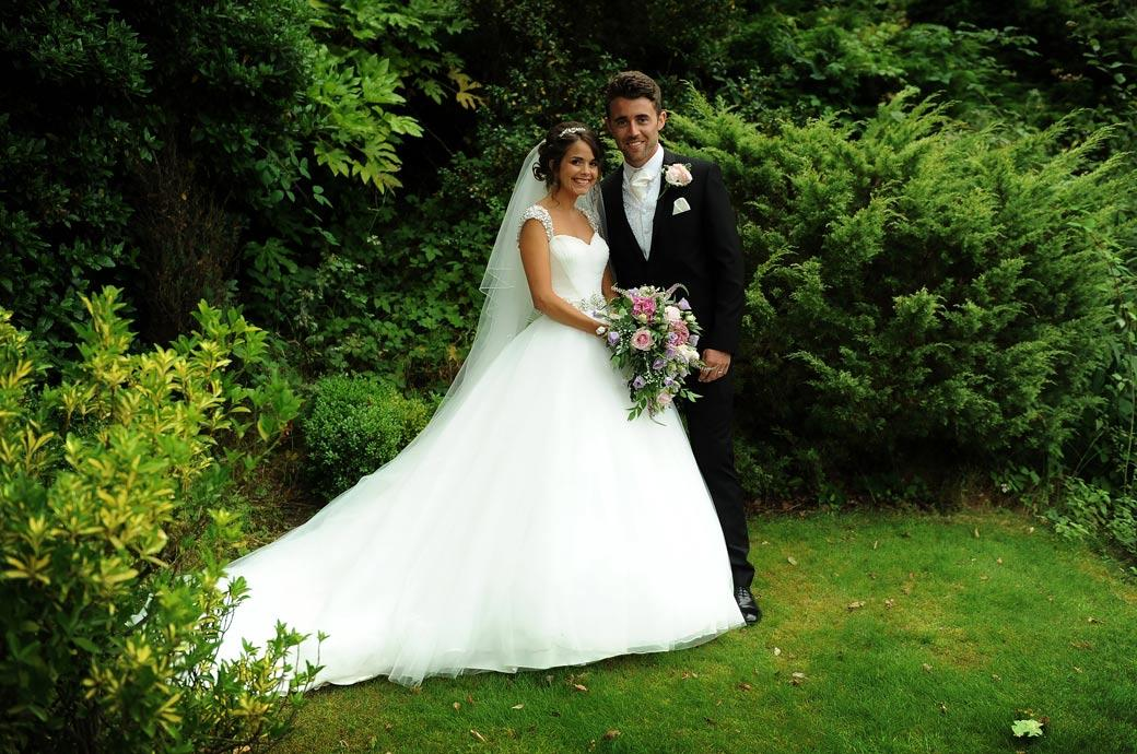 The happy newly-weds stand for a wedding photo in front of the green and mature shrubs in the scenic Hever Castle Golf Club gardens which make this such a fine Kent wedding venue