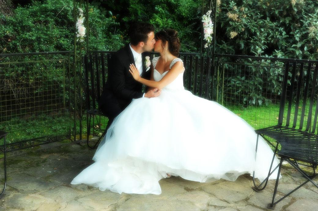 A beautifully romantic wedding picture of the Bride and Groom kissing under the gazebo taken at Hever Castle Golf Club by Surrey Lane wedding photographers