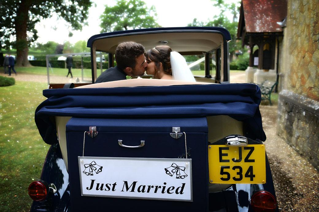 A romantic wedding photograph of the newly-wed couple kissing in the back of the bridal car outside the church on route to Hever Castle Golf Club a beautiful wedding venue in Kent