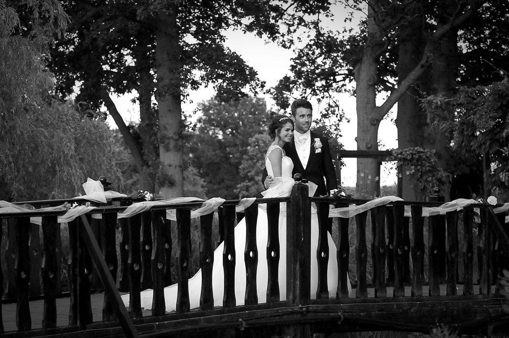Wedding picture of the romantic couple at Hever Castle Golf Club standing on the bridge looking out over the ornamental pond and watching their guests having fun at this fine Kent wedding venue