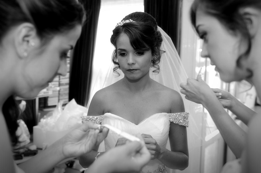 A nervous Bride watches as her Bridesmaids make necessary adjustments in this wedding picture taken prior to leaving for St Paul's Church Four Elms and Hever Castle Golf Club  in Kent