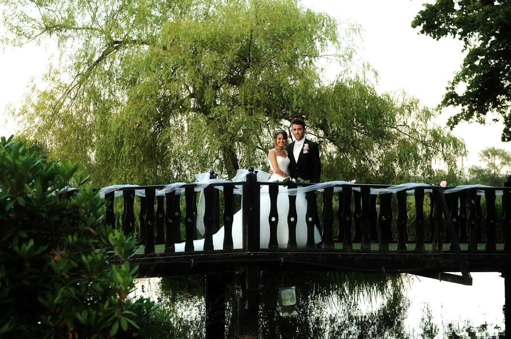 Romantic wedding photo of the Bride and Groom as they stand on the bridge over the ornamental pond at Kent wedding venue Hever Castle Golf Club