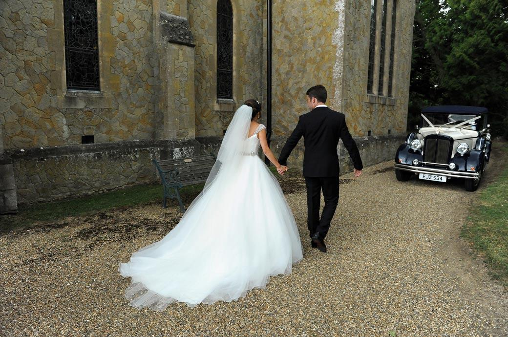 Groom taking his fairytale Bride towards the Bridal car to leave for the nearby Kent wedding venue Hever Castle Golf Club after their St Paul's Church Four Elms marriage cermeony