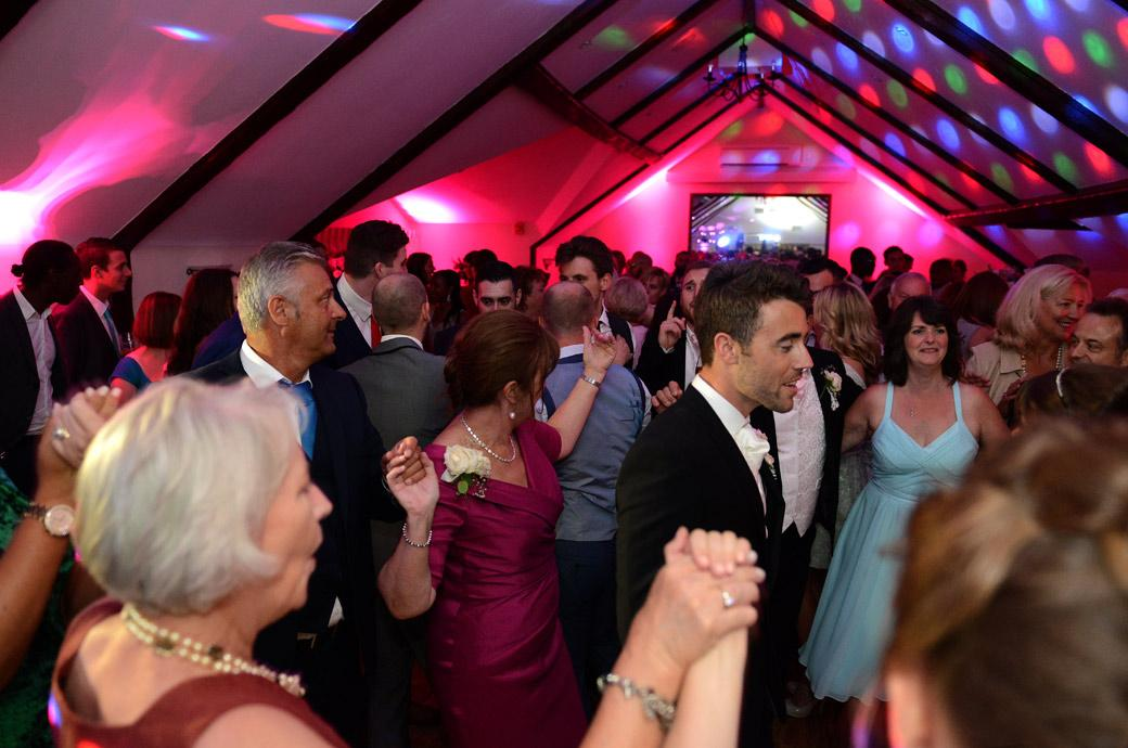 A packed dancefloor in the Princes Suite as everyone gets down dancing in this fun and colourful wedding photo by Surrey Lane wedding photography at Hever Castle Golf Club