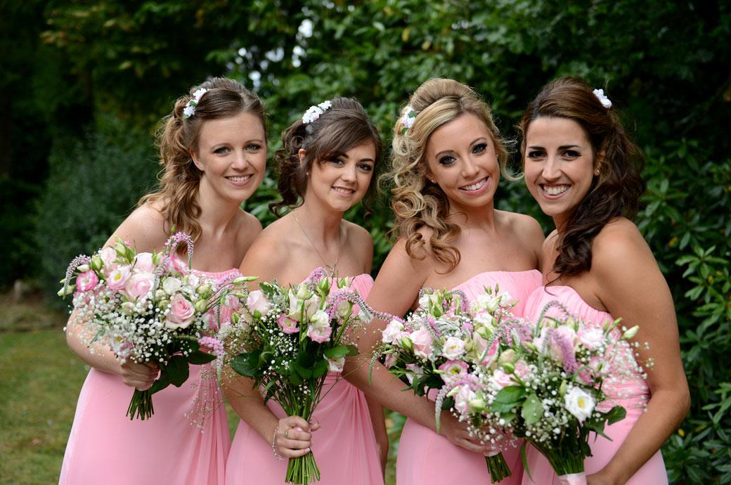 Four lovely Bridesmaids in pink all smiles for a wedding photo outside St Paul's Church Four Elms just before they leave for Hever Castle Golf Club another Kent wedding venue down the road