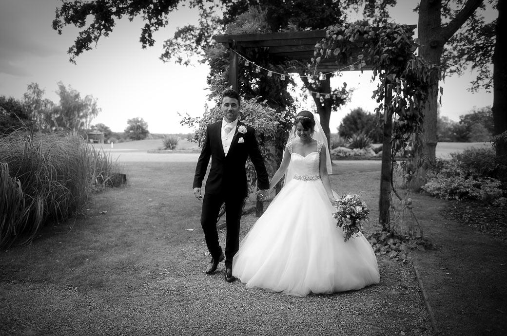 Happy serene newly-weds walk to the bridge over the ornamental pond for some wedding pictures during a Hever Castle Golf Club reception captured bty Surrey Lane wedding photography