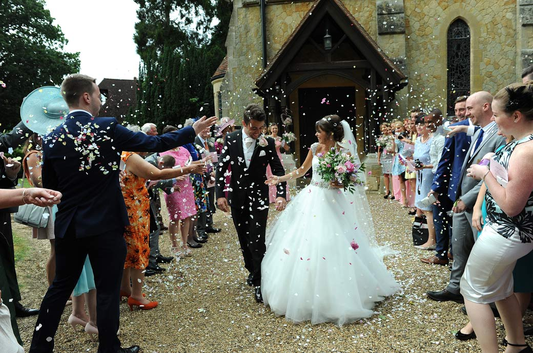 Confetti fun time for the Bride and Groom outside Kent wedding venue St Paul's Church Four Elms captured in this wedding picture by Surrey Lane wedding photography
