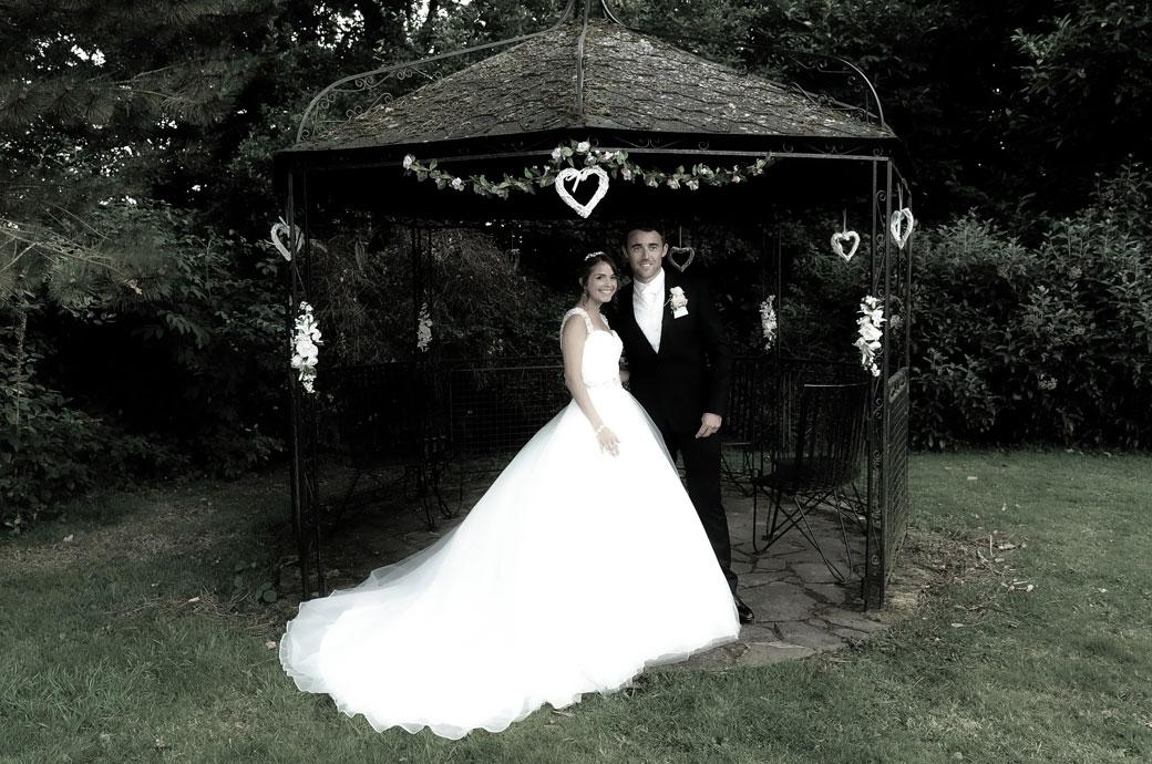 The proud Groom and his beautiful Bride stand by the gazebo for some romantic wedding photographs in the picturesque Hever Castle Golf Club gardens
