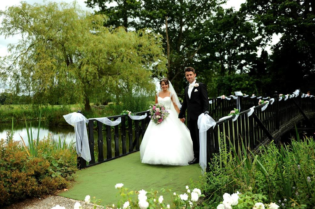 Hever Castle Golf Club newly-wed couple standing at the end of the bridge over the ornamental pond in this wedding photograph taken by Surrey Lane wedding photography