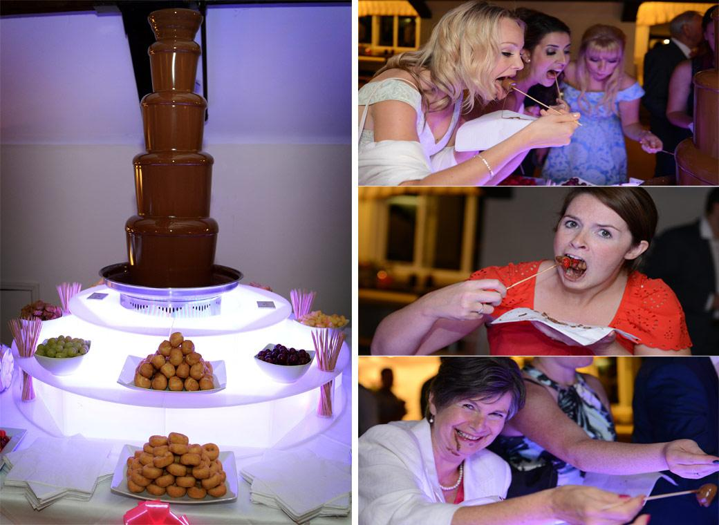 Guests tuck in to the chocolate fountain in these fun wedding pictures captured in the Hever Castle Golf Club bar by Surrey Lane wedding photography in Kent