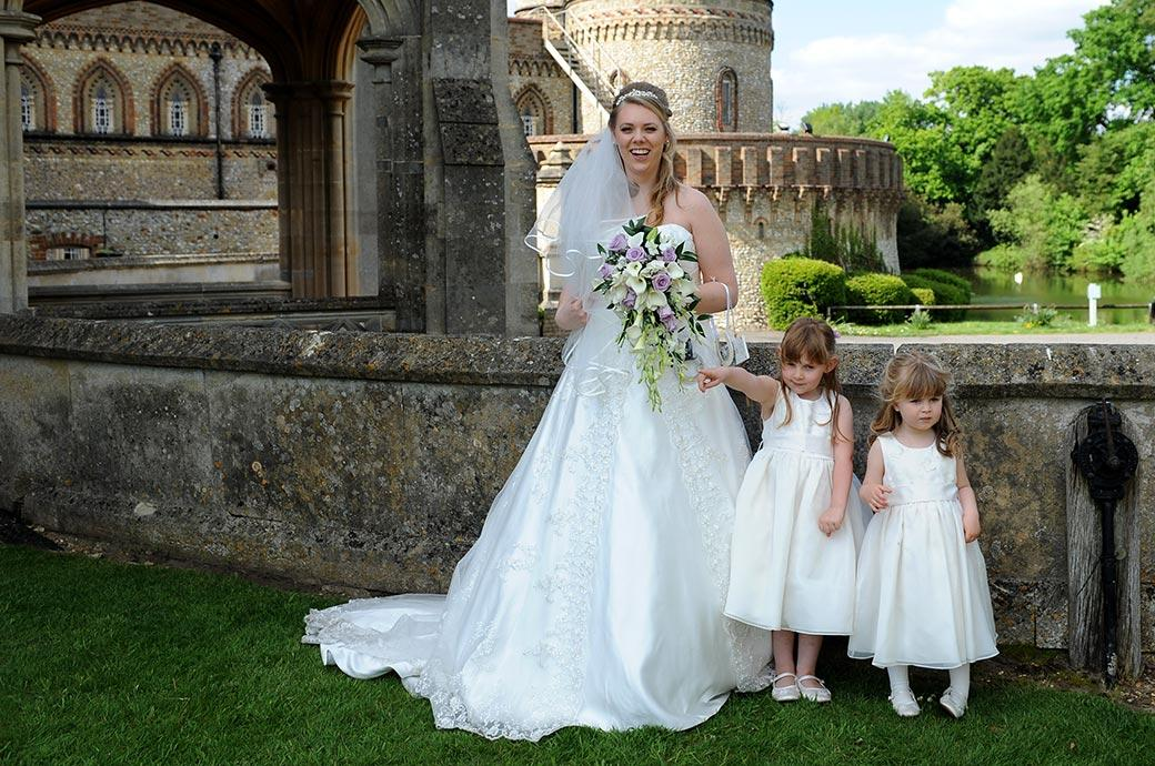 The lovely smiling Bride stands with her cute flower girls at Surrey wedding venue Horsley Towers as they await the arrival of the groom for the group wedding photos