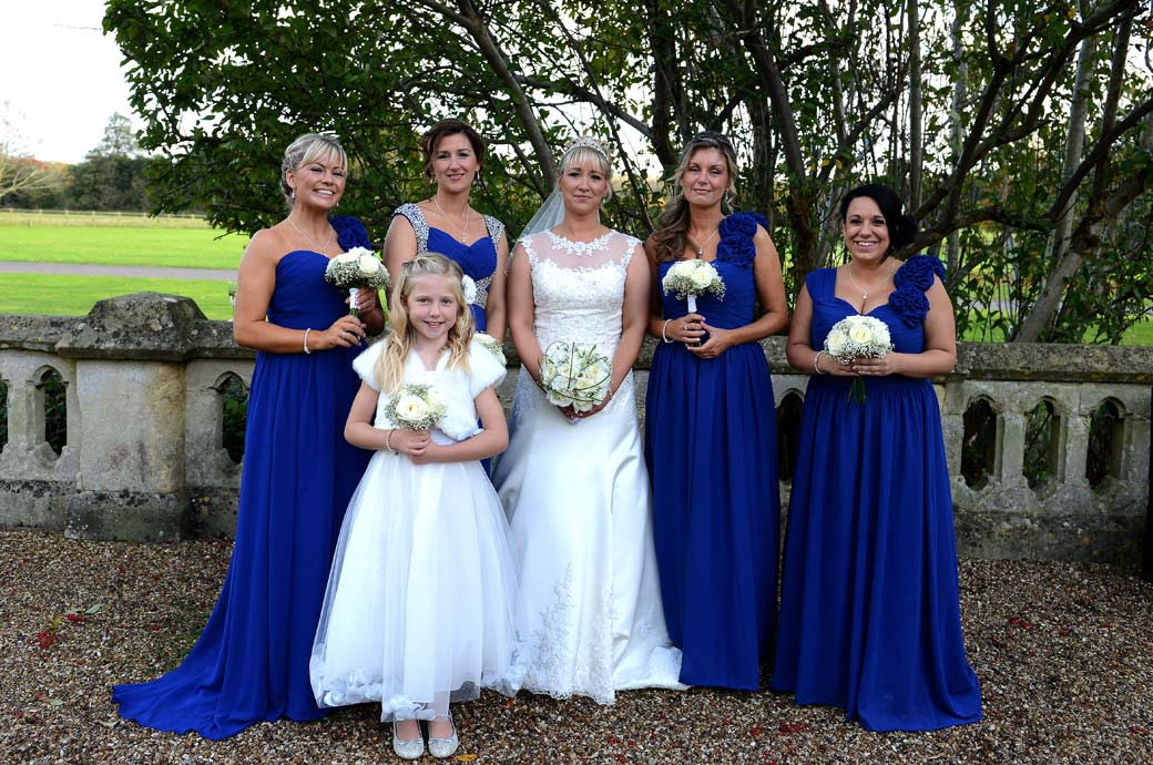 The Bride and Bridesmaids all looking lovely in white and blue with their bouquets in this bright and colourful wedding photograph taken at Surrey wedding venue Horsley Towers