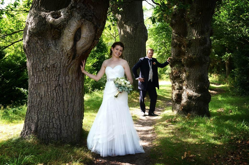Fun  wedding picture of the Bride and Groom standing by separate trees taken at Horsley Towers by Surrey Lane wedding photography