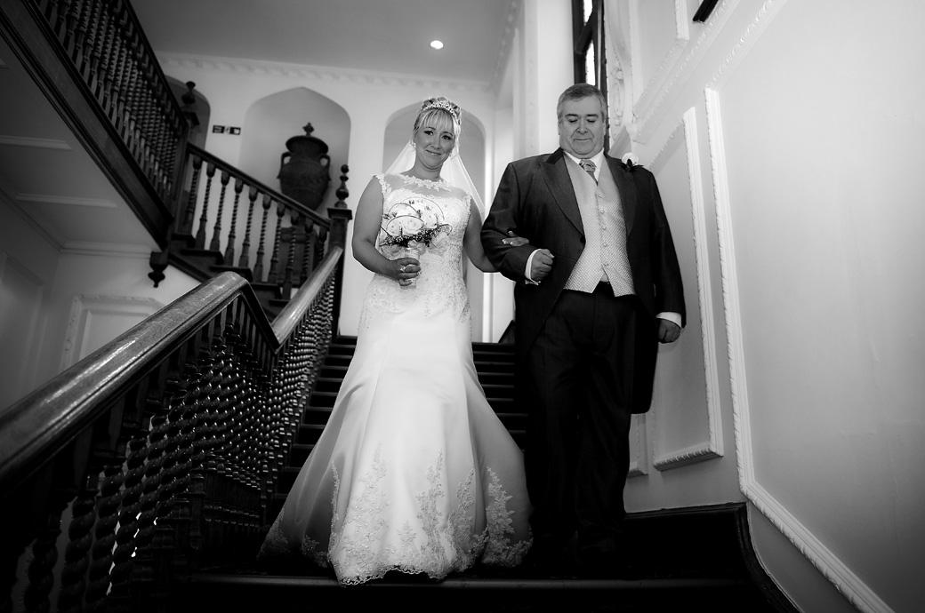 A beaming Bride descending the stairs on the arm of her father on their way to the Sopwith Room captured in this wedding picture taken at Horsley Towers by Surrey Lane wedding photographers