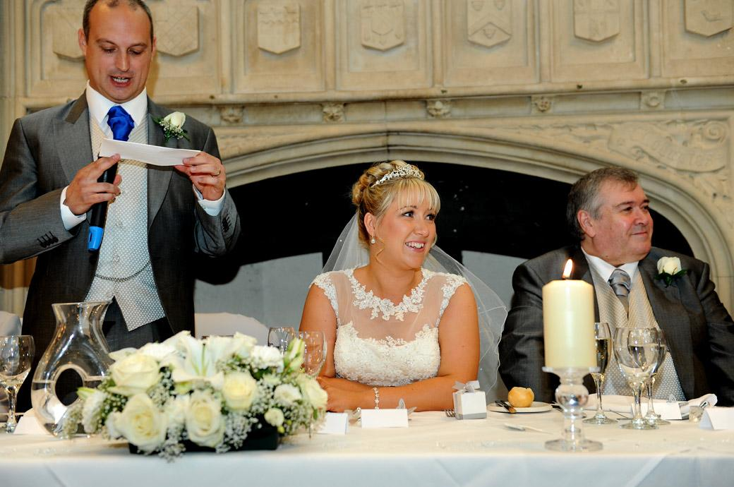 The Bride smiles as she listens to her husband's speech in this wedding photograph taken in the Great Hall at Horsley Towers a magical wedding venue in Surrey