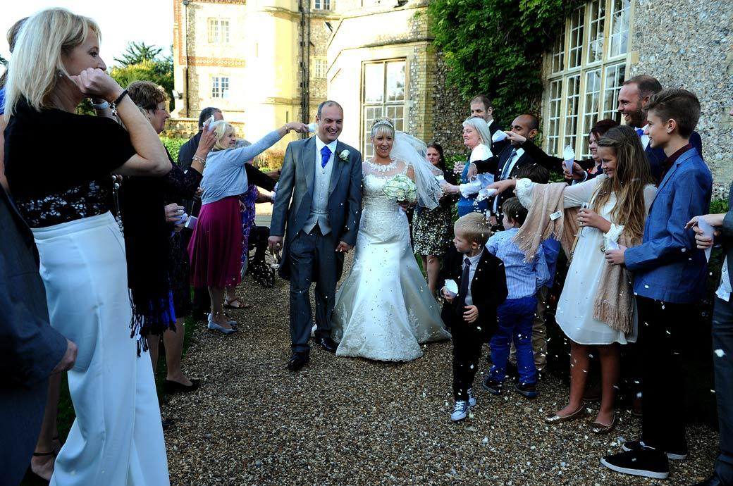 Newly-weds at the beginning of the walk past the guests for the confetti  throwing captured in this wedding photo by Surrey Lane wedding photographers in the grounds of Horsley Towers