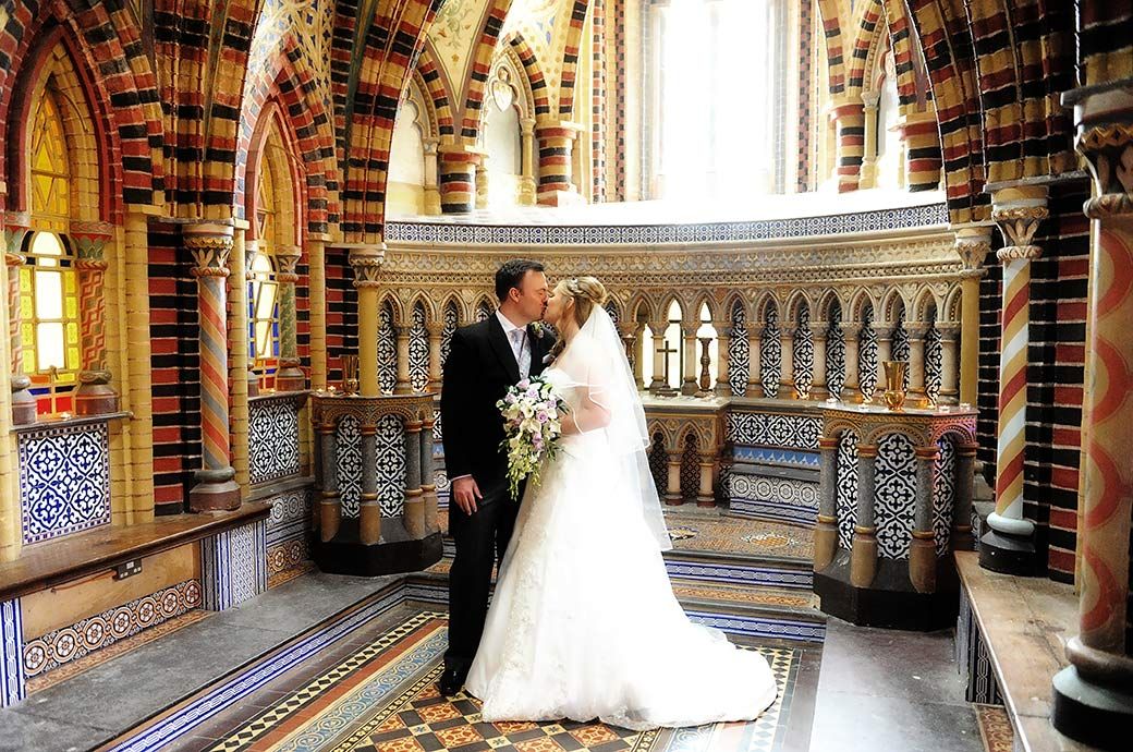 Bride and groom captured in this wedding photo as they romantically kiss at Surrey venue Horsley Towers in the colourful and elaborately tiled chapel