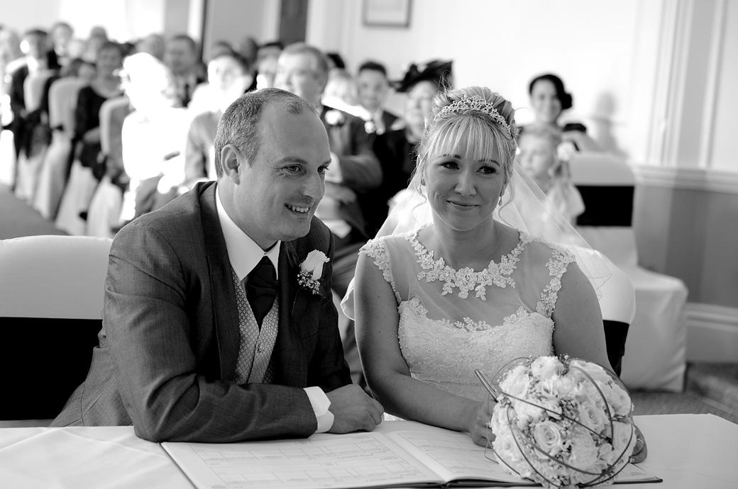 Happy newly-weds pose for a wedding picture as they sign the marriage register in the Sopwith Room at Horsley Towers captured by a Surrey Lane wedding photographer