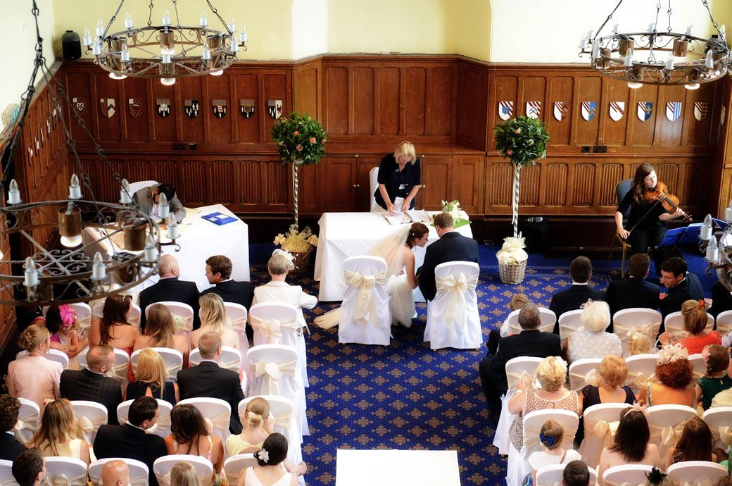 A discrete wedding  photo of an intimate moment taken from the balcony of the Great Hall at Horsley Towers and captured by a Surrey Lane wedding photographer