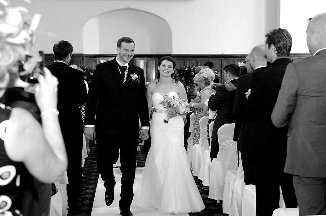 A joyful beaming Bride and Groom walk down the aisle in the Great Hall as husband and wife in this happy wedding photo taken at Surrey wedding venue Horsley Towers