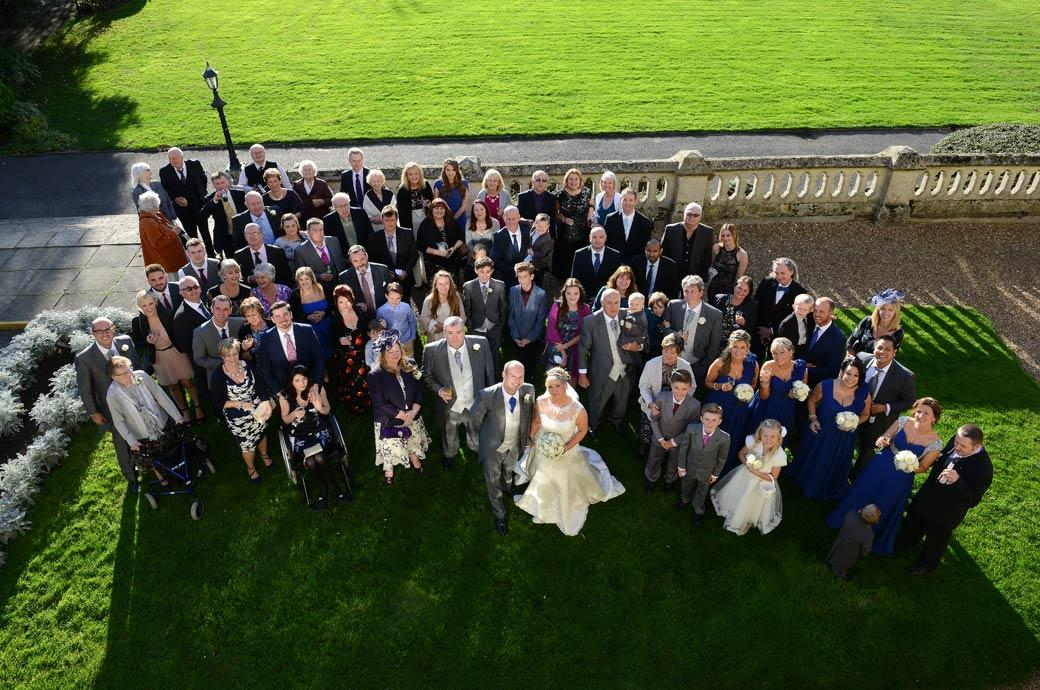 The everyone wedding picture captured by the Surrey Lane wedding photographer standing high up on the roof of The Sopwith Room at Horsley Towers