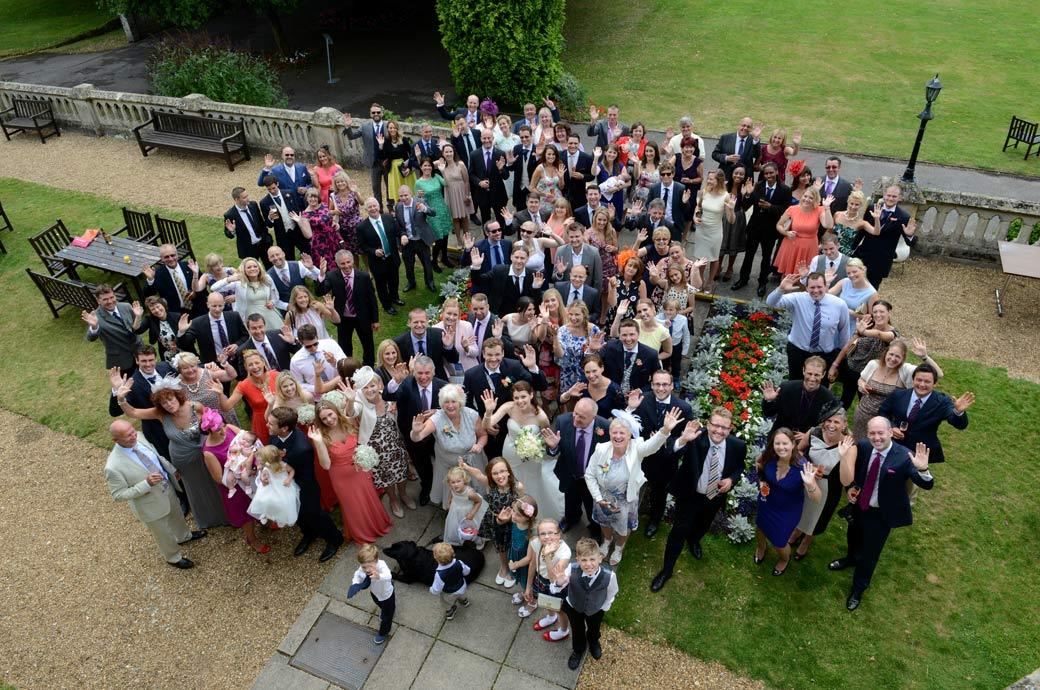 Guests looking up and waving in this everyone group wedding picture taken in the garden at Surrey wedding venue Horsley Towers by a photographer up high on the roof