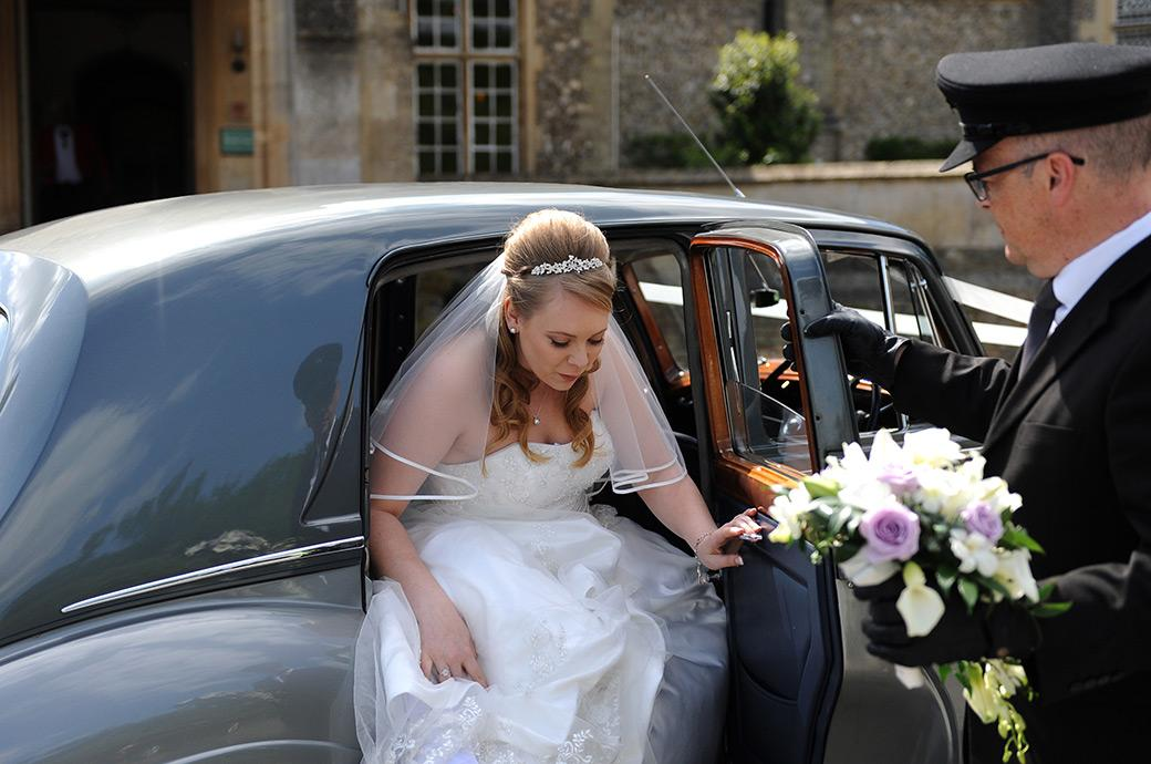 An excited Bride carefully gets out of the Rolls Royce on her way to get married captured in this wedding photo from the magical Surrey wedding venue Horsley Towers