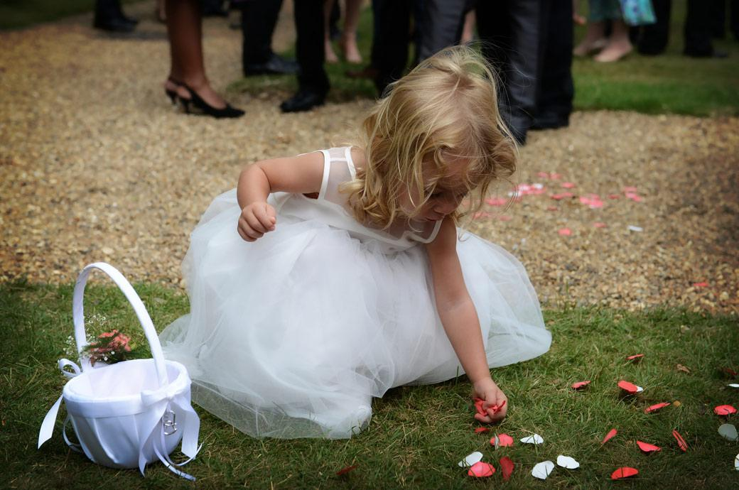 A beautiful wedding photo of a sweet little flowergirl picking up rose petals from the lawn captured by Surrey Lane wedding photography at the wonderful venue Horsley Towers