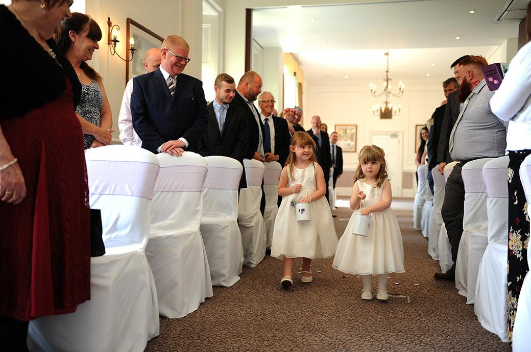 Wedding picture of two cute little flower girls at Surrey wedding venue Horsley Towers dropping petals down the aisle of the Sopwith Room