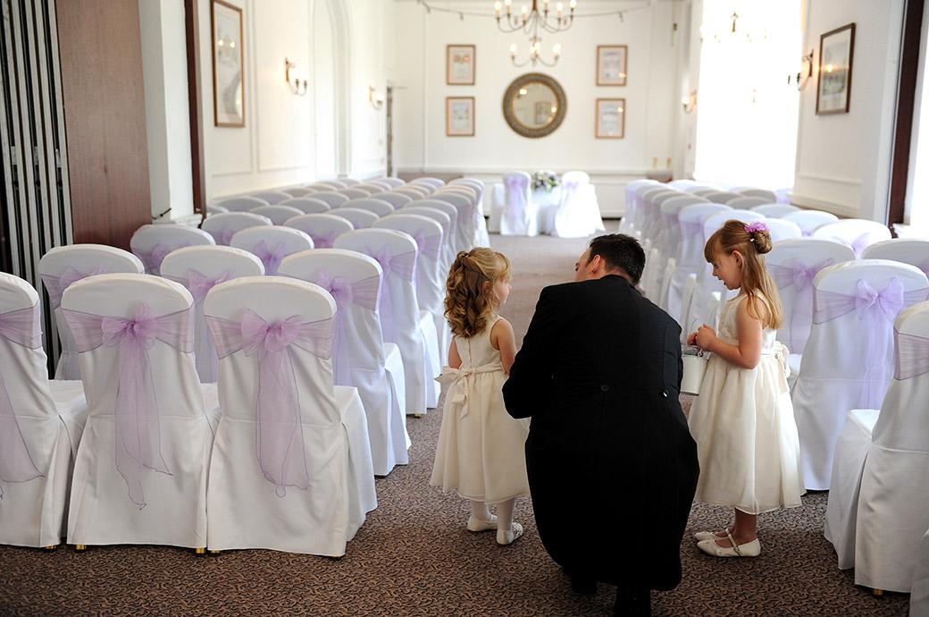 Cute wedding picture of the Groom instructing the flower girls at Surrey wedding venue Horsley Towers how to walk down the aisle of the Sopwith Room