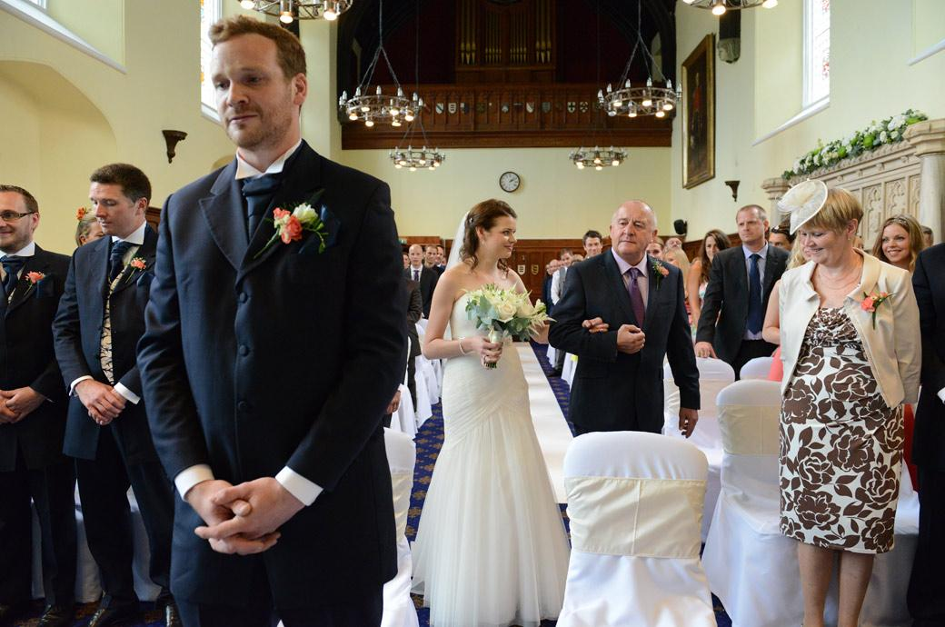 The Groom standing with nervousness as he awaits the appraoching Bride in this wedding photograph taken in the aisle of the Great Hall of  Horsley Towers a fine Surrey wedding venue