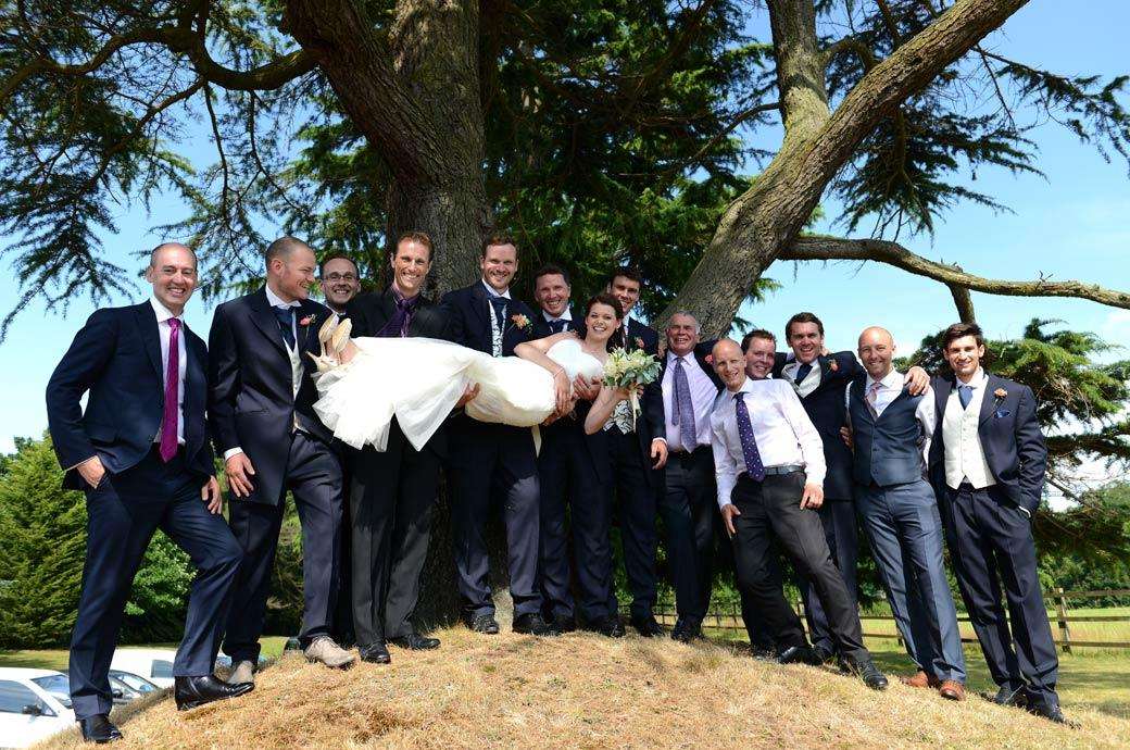 The happy Groom holds up his beaming Bride accompanied by the gents in this wedding photograph taken on a hillock overlooking the Surrey wedding venue Horsley Towers