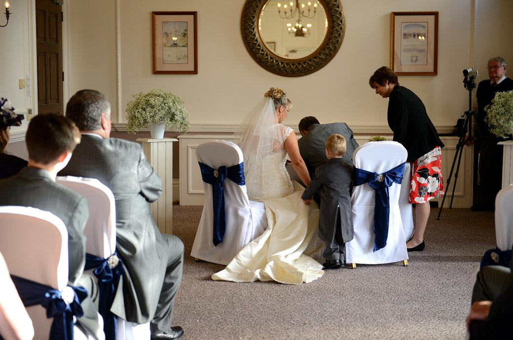 Sweet wedding photograph of the Groom signing the marriage registrar as the bride holding her little son's hand looks on in the Sopwith Room at Surrey wedding venue Horsley Towers