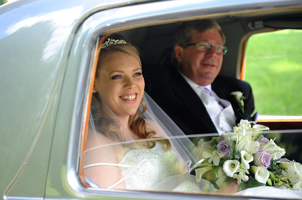 Happy and excited smiling Bride captured in this wedding photo outside Horsley Towers Surrey as she sits with her father in her Rolls Royce bridal car