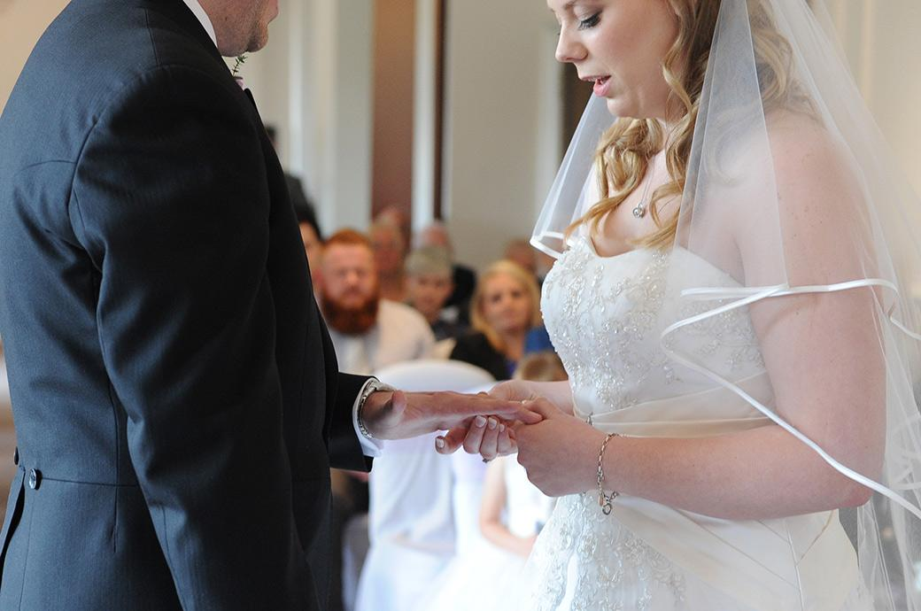 Bride says her marriage vows as she pushes the wedding ring onto the groom's finger in the Sopwith Room at wedding venue Horsley Towers in  Surrey