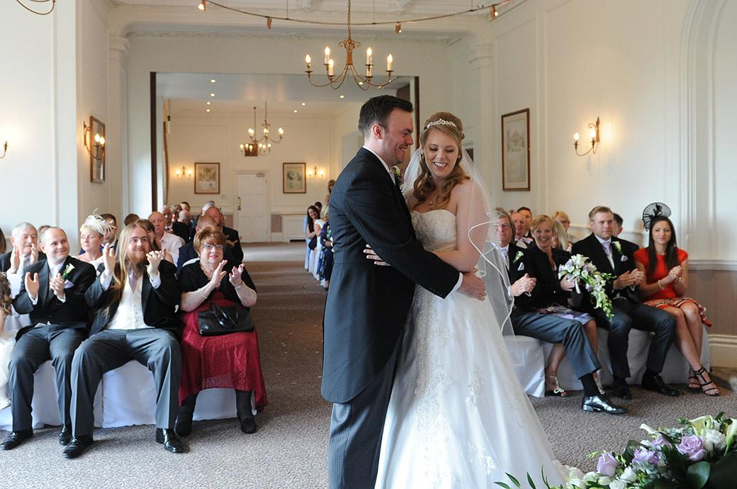 Happy Bride and Groom hug and guests clap and cheer at Horsley Towers Surrey after they are announced husband and wife in the Sopwith Room