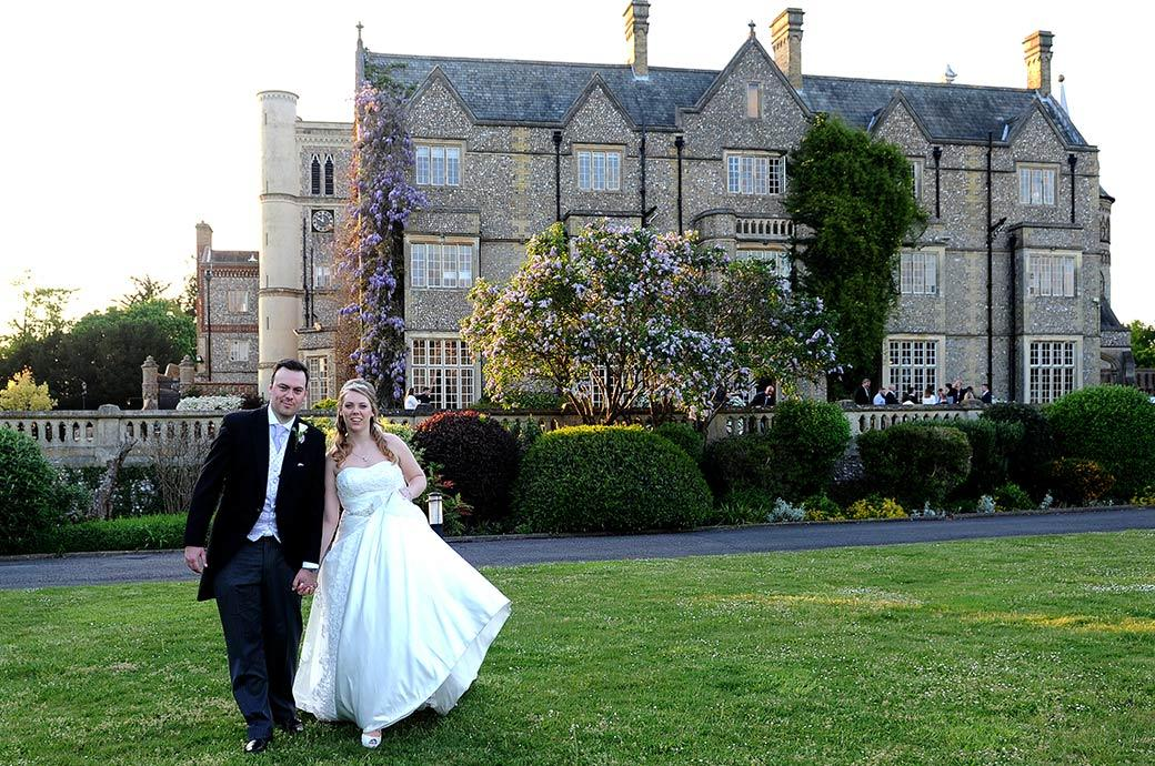Relaxed and happy Bride and groom walking across the grass hand in hand after getting married earlier at Surrey wedding venue Horsley Towers in the Sopwith Room