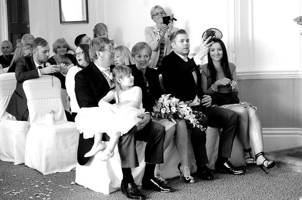Happy wedding guests taking mobile phone pictures of the newlyweds from the front row in the Sopwith Room at the Horsley Towers Surrey wedding venue
