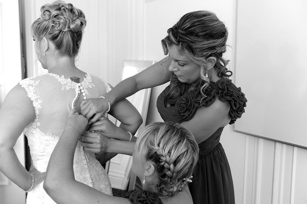 Bridesmaids busy fastening up the Bride's dress in this final getting ready wedding photo captured at the wonderful Horsley Towers by Surrey Lane wedding photography