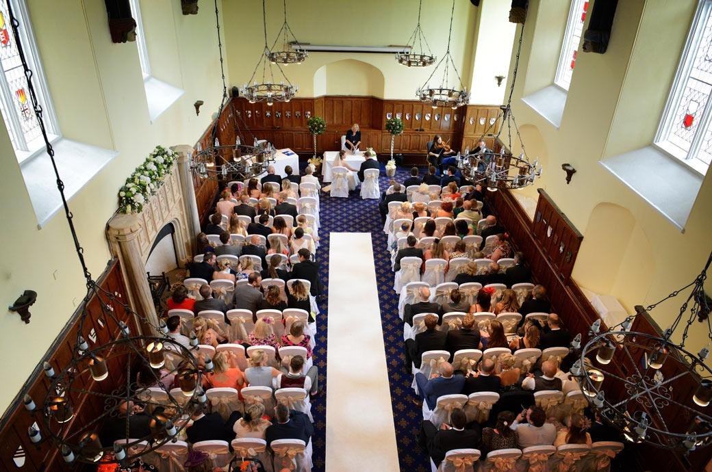 A balcony wedding picture taken of the seated guests and newly-weds waiting to sing the marriage register taken in the Great Hall of Surrey wedding venue Horsley Towers