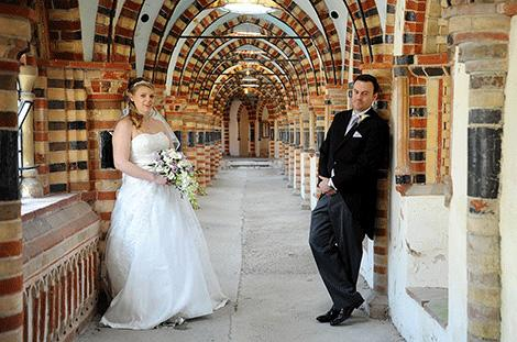 Relaxed newlyweds strike a pose in the unusual and memorable cloisters situated in the ever popular Horsley Towers Surrey wedding venue in the village of East Horsley