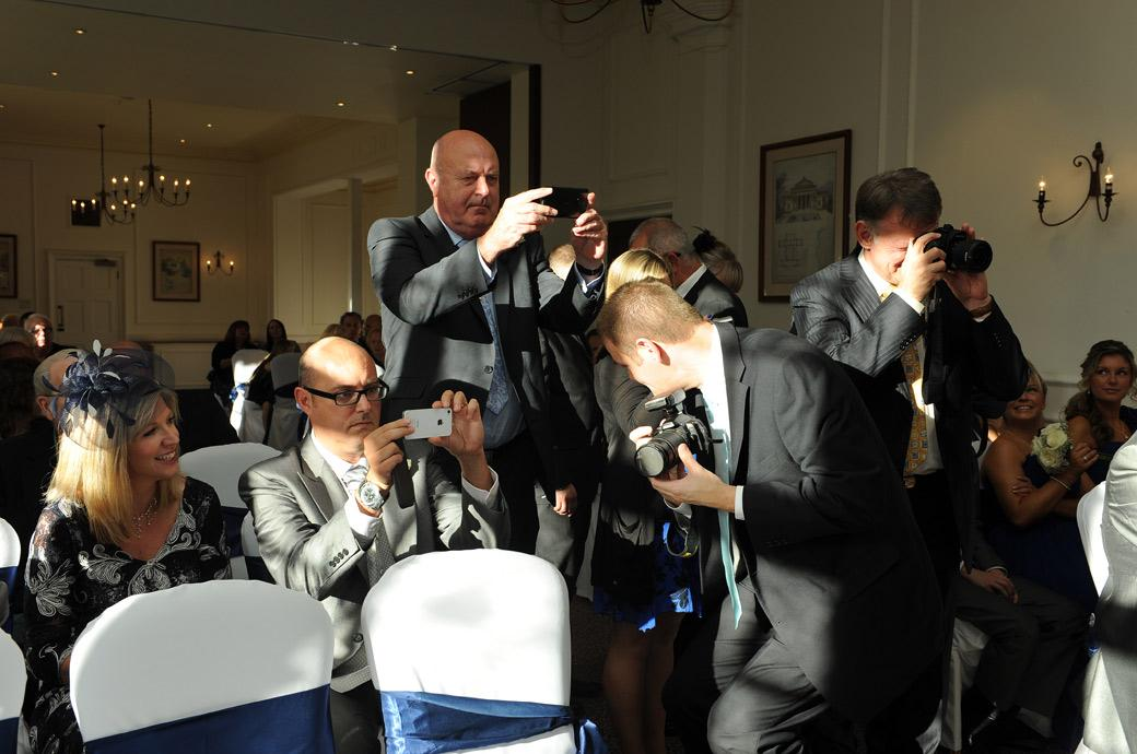 Guests jump up and scramble for that perfect wedding photo of the newly-weds signing the marriage register in the Sopwith Room at Horsley Towers in Surrey