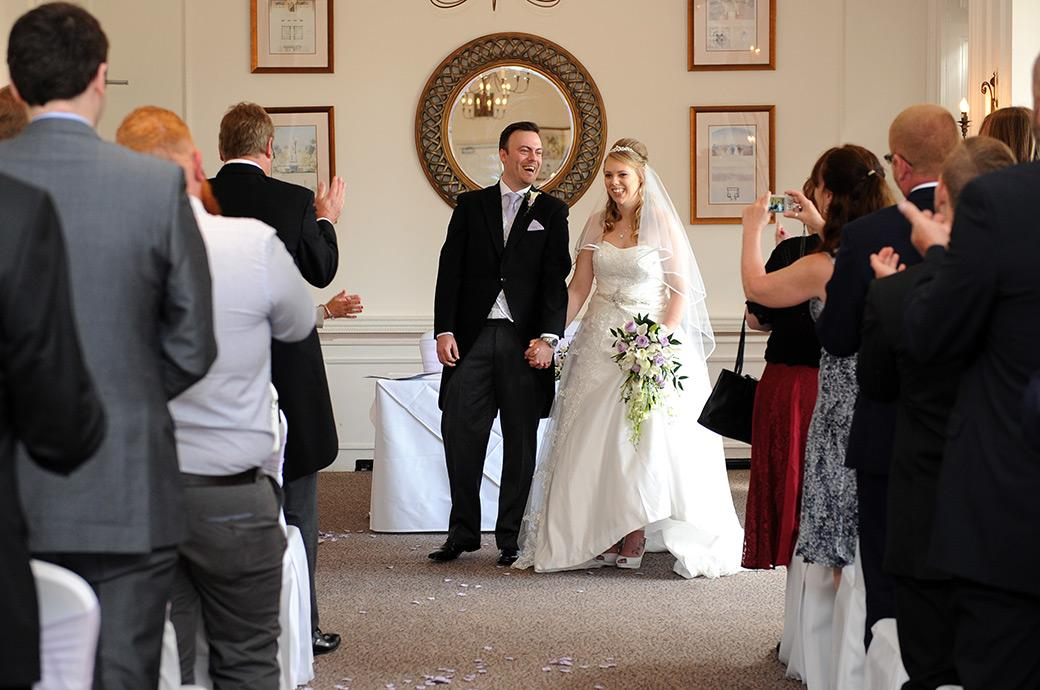 Bride and groom smile with joy as they get ready to walk down the aisle of the Sopwith Room in this wedding picture from Horsley Towers wedding venue Surrey