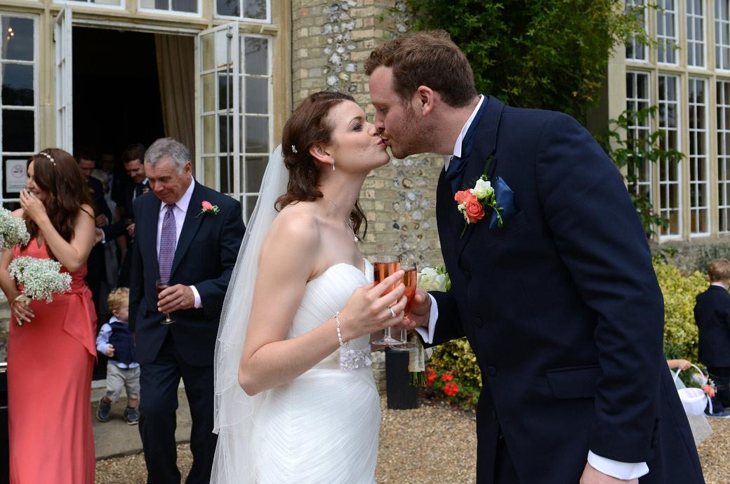 Glasses of rosé and a relaxed fun loving kiss captured in this informal wedding photograph taken of the newly-weds at Horsley Towers by Surrey Lane wedding photography