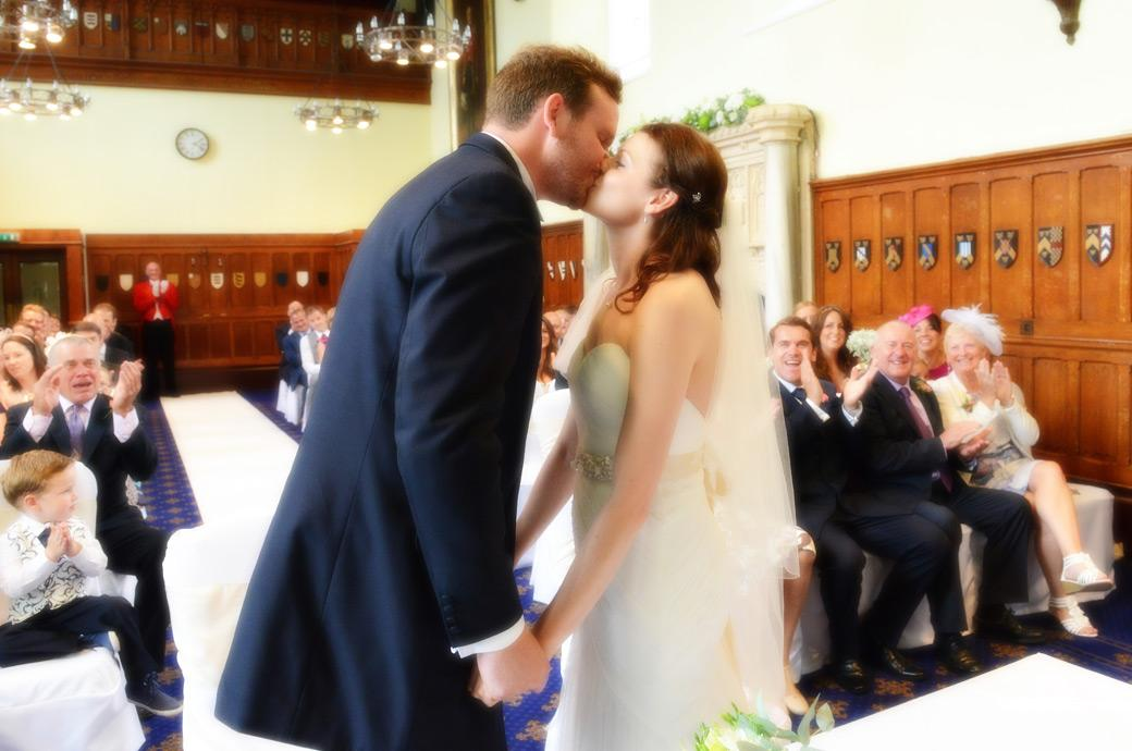 Newly-weds kiss to much clapping and cheering in the Great Hall delightfully captured in this wedding photograph from Horsley Towers by Surrey Lane wedding photography