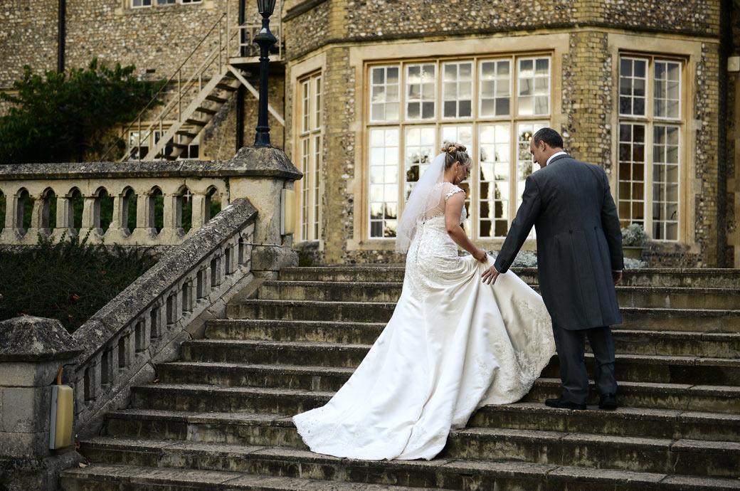 The Groom is ready to help the Bride with her dress in this wedding picture taken as they ascend the stone steps leading up to the Sopwith Room at Horsley Towers in Surrey