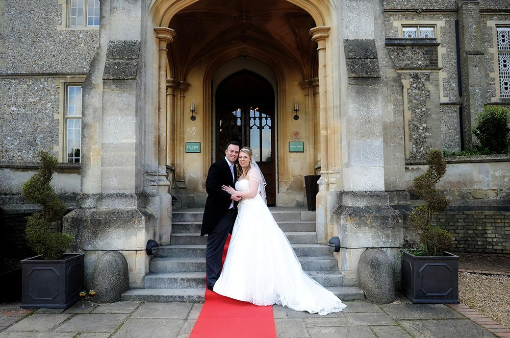 Smiling newlyweds head on head captured in this wedding photo from Surrey wedding venue Horsley Towers as they stand on the red carpeted steps