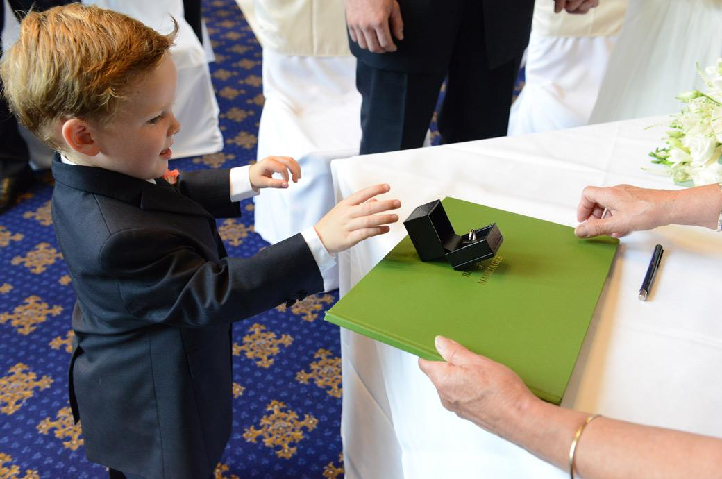 Cute pageboy hands over the marriage rings to the registrar in this sweet wedding photo by Surrey Lane wedding photographers at the magnificent Horsley Towers
