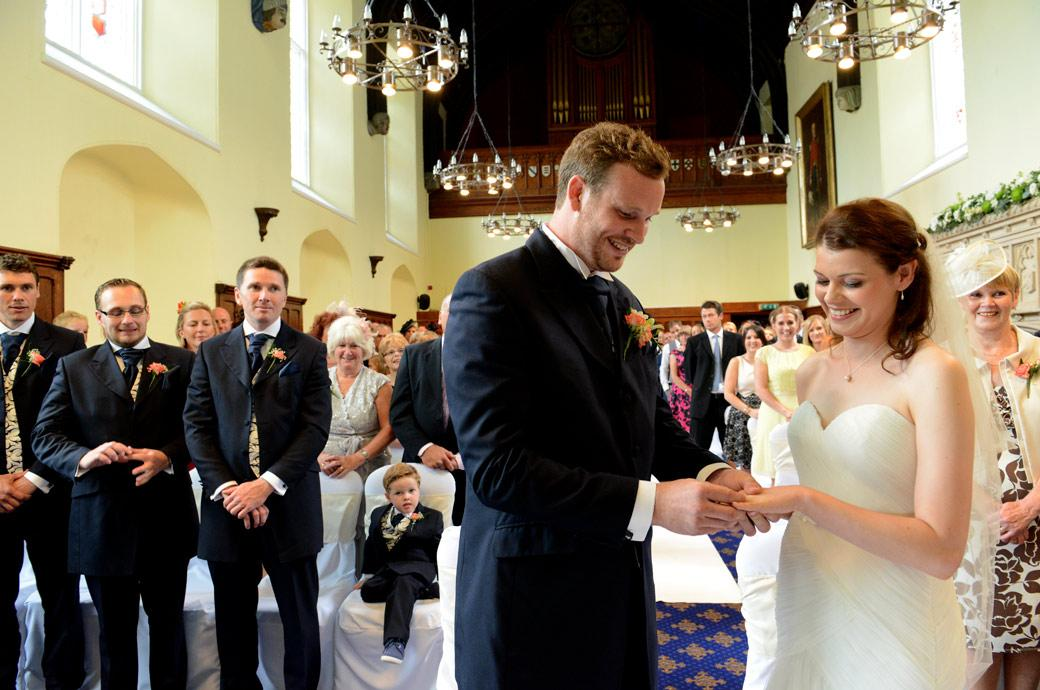 Smiling Groom places the marriage ring on a smiling Bride's finger in this lovely wedding photograph taken in the Great Hall at Horsley Towers a fabulous Surrey wedding venue